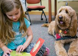 Child reading to therapy dog at Macon County Public Library